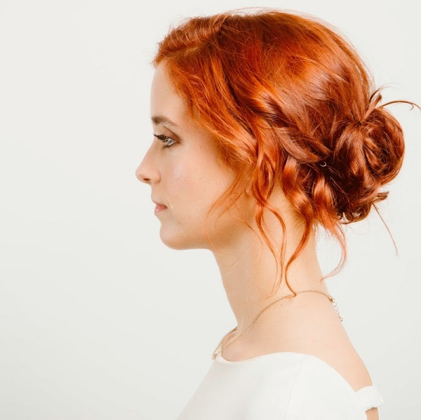Mujer con pelo cobrizo dando elegancia y haciéncola lucir elegante y natural