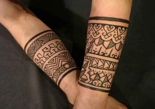 Joven con los brazos tatuados con muñequeras estilo tribal