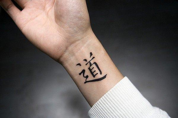 Joven hombre con un tatuaje con símbolos orientales en su brazo