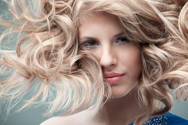 Mujer con cabello teñido de rubio y sus pelos al viento