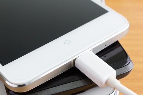 un celular con su cargador conectado a la corriente