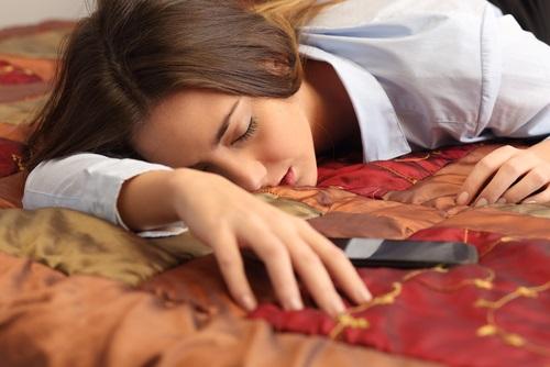 Mujer que sufre problemas para conciliar el sueño por tener el celular cerca