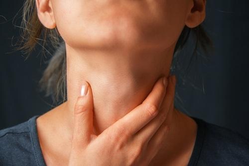 Mujer joven con dolor de garganta por causa de la enfermedad del beso