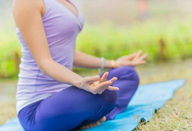 Una mujer joven haciendo yoga en el exterior