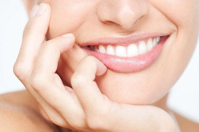 Mujer luciendo una sonrisa perfecta usando implantes