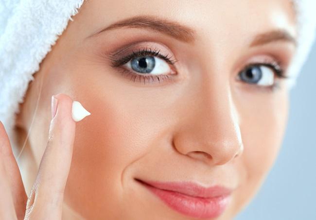 joven mujer haciendo una limpieza facial con cremas hidratantes y gel