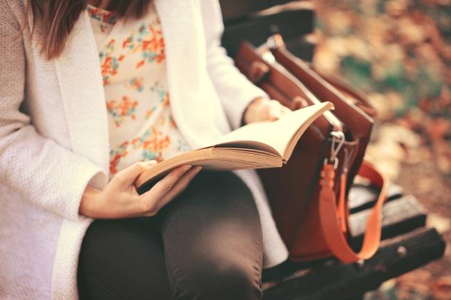 Una mujer adulta leyendo sentada en un parque