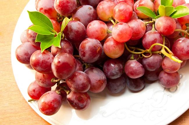 Un plato con uvas rojas que se ven deliciosas