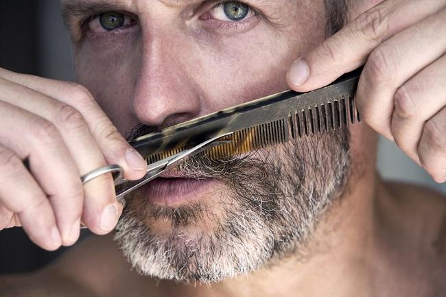 Hombre adulto peinando su barba que luce con canas