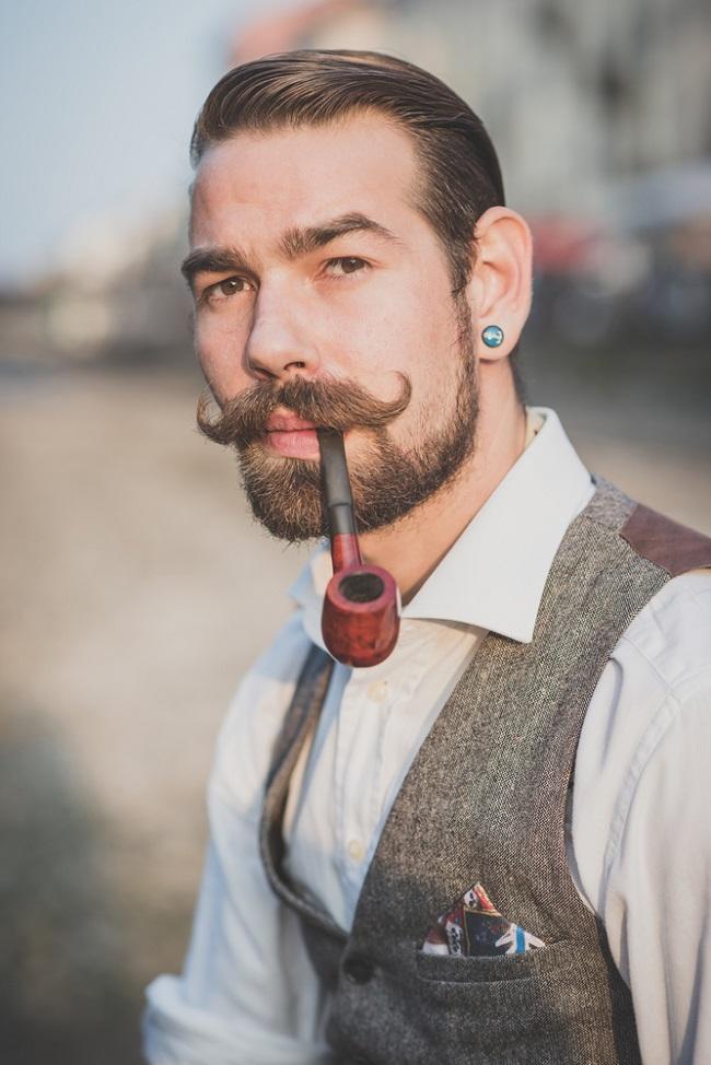 Joven con un look retro que ha dejado crecer su bigote y está fumando pipa