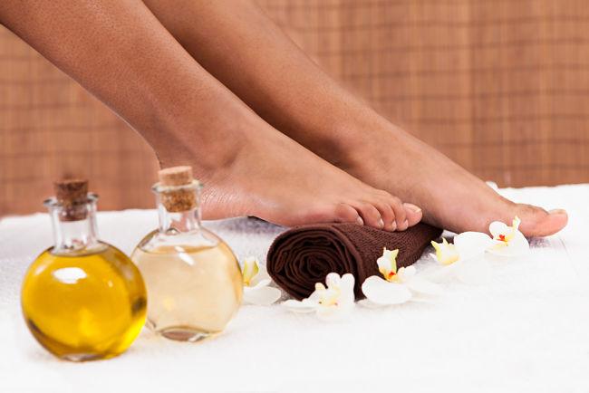 Mujer con piernas depiladas y aceite de oliva para hidratar la piel