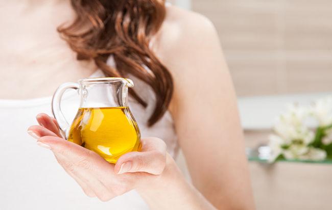 Mujer usando aceite de oliva para dar brillo a su cabello