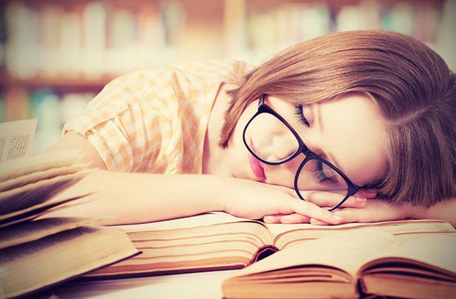 Mujer se queda dormida sobre un libro