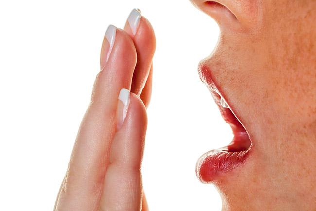 mujer poniendo su mano en la boca para detectar el mal aliento