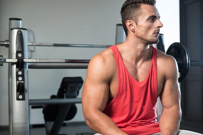 Hombre en el gimnasio haciendo levantamiento de pesas para aumentar la masa muscular