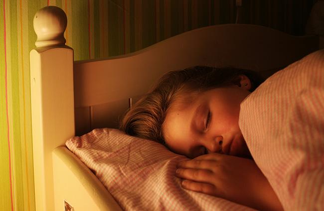 Mujer durmiendo sobre la cama con la luz del velador encendida