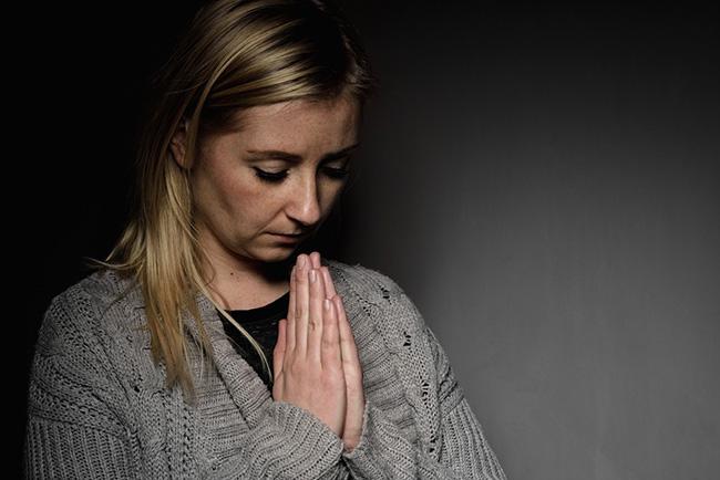 Mujer orando y pidiendo perdón