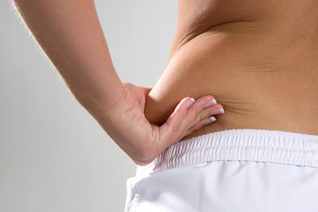Mujer que padece grasa en la cintura y la agarra con su mano
