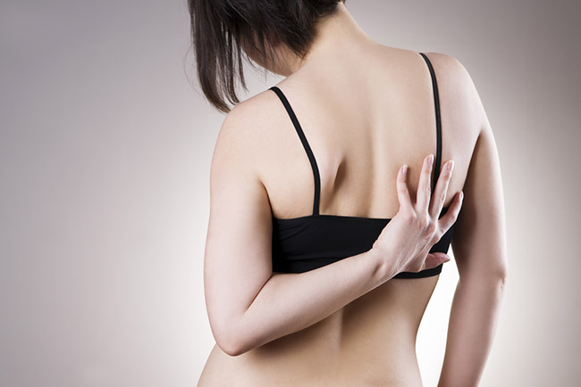 mujer realiza ejercicios para aliviar el dolor de espalda