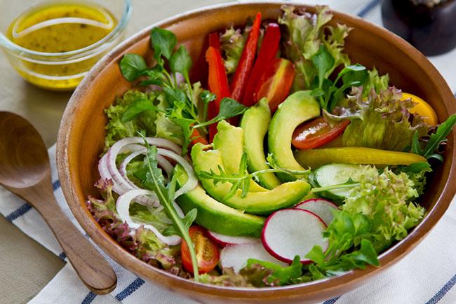 Un plato de ensalada con aguacates y verduras para eliminar las lonjas de la cintura
