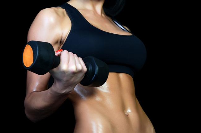 Mujer entrenando con pesas para aumentar masa muscular