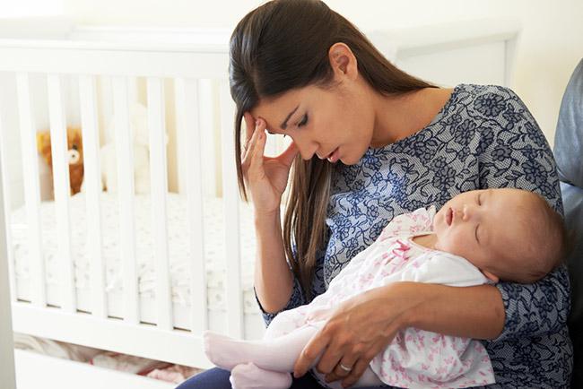 Mujer cargando un bebé y con depresión y fatiga