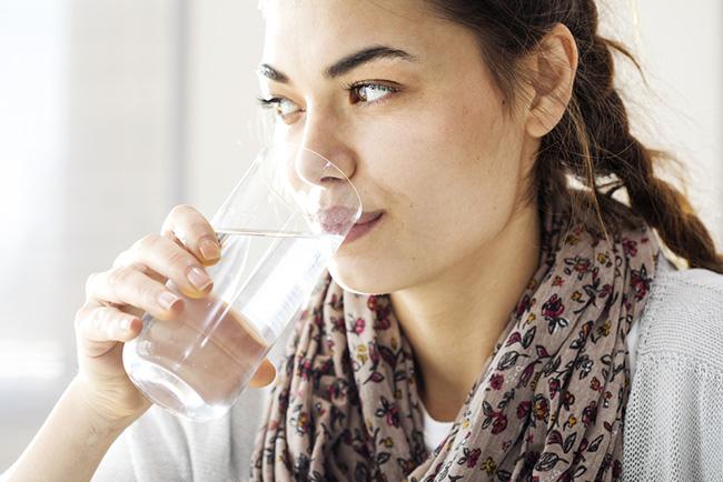 Mujer tomando un vaso de agua para aliviar el hipo persistente