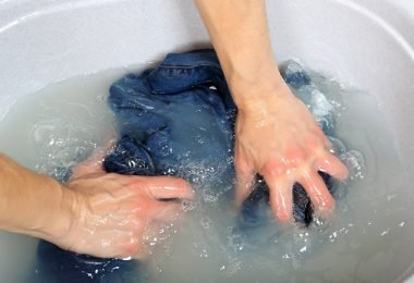 Prenda de ropa sumergida en el agua para quitar las manchas de tinta