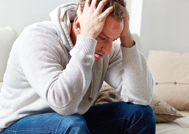 Hombre se toma su abeza por ansiedad sufrida por andropausia