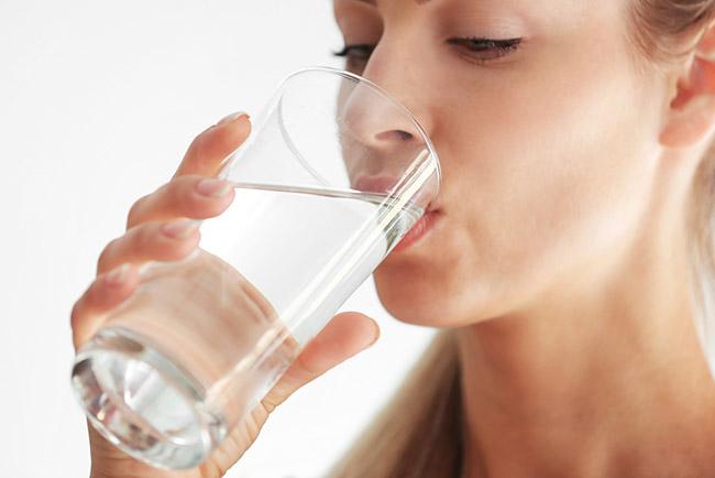 Mujer obteniendo los beneficios de beber agua tibia