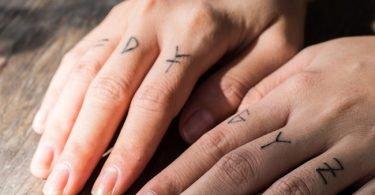 Hombre con tatuajes de petras en sus dedos