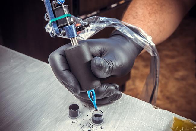 Tatuador realizando carga de tinta para hacer un tatuaje