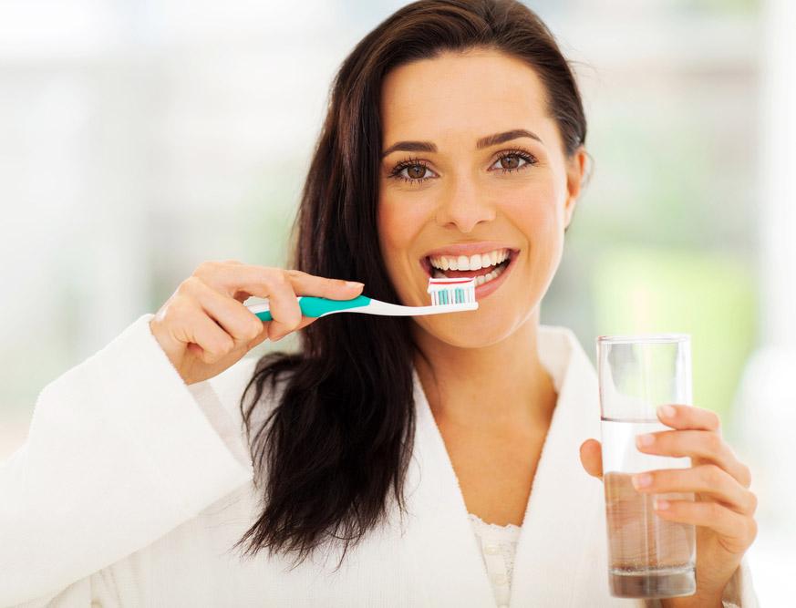 Mujer joven realizándose una limpieza bucal