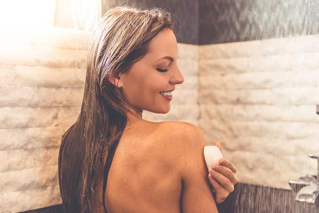Mujer usando jabón de perejil para eliminar las manchas dle rostro