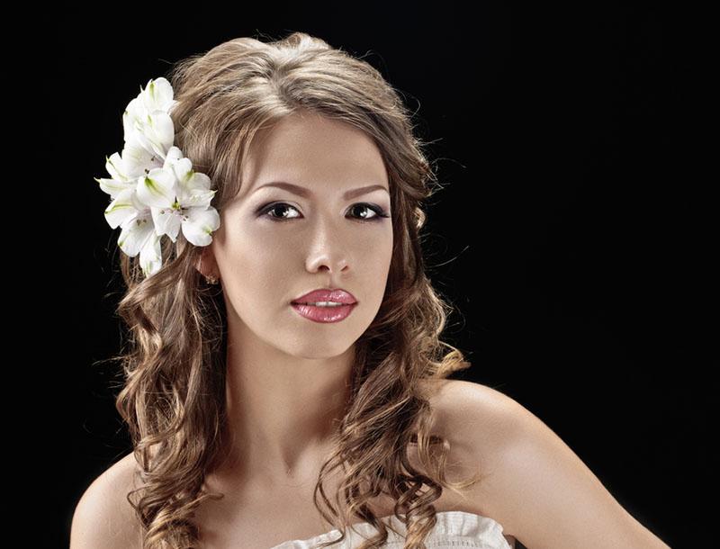 Joven mujer dejando su cabello suelo con una flor al costado, un clásico look de novia en primavera