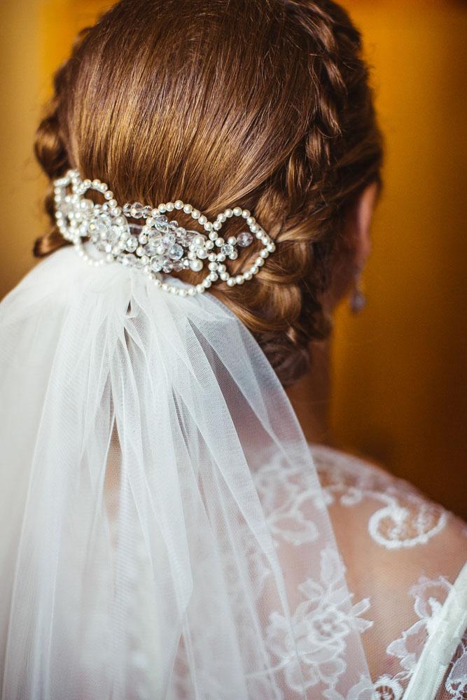 Novia luciendo un peinado tradicional de una corona con trenzas y velo