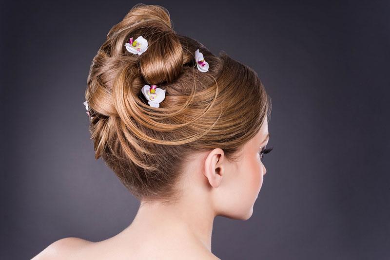 Mujer luciendo los peinados de novia que vuelven, los retros con flores y rodetes