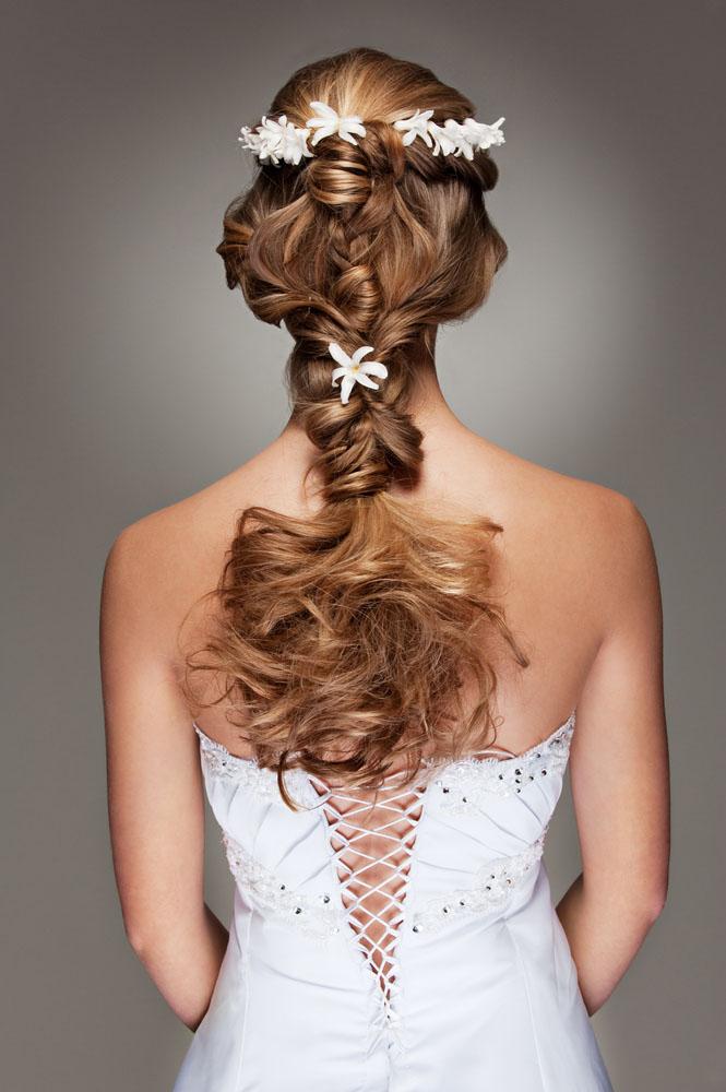 Chica joven con pelo rubio que se va a casar luce un peinado con trenzas