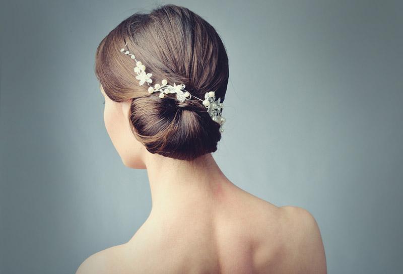 Mujer luciendo un peinado para boda con recogido de lado