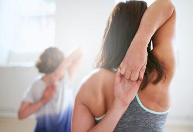Mujer practicando postura de yoga para tonificar el busto