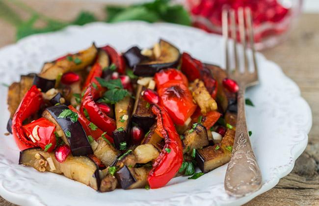Berenjenas acompañadas con verduras servidas en un plato blanco