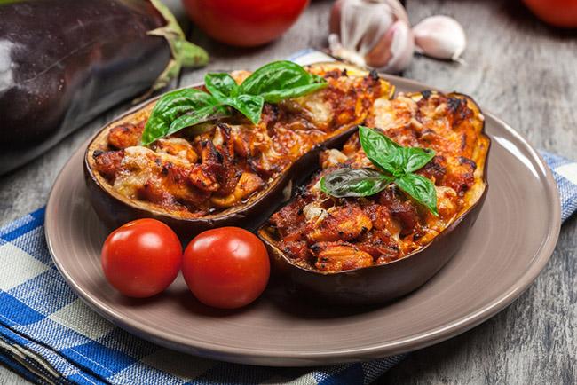 Unas berenjenas rellenas con arroz servidas en un plato acompañadas de tomate para una receta vegana imperdible