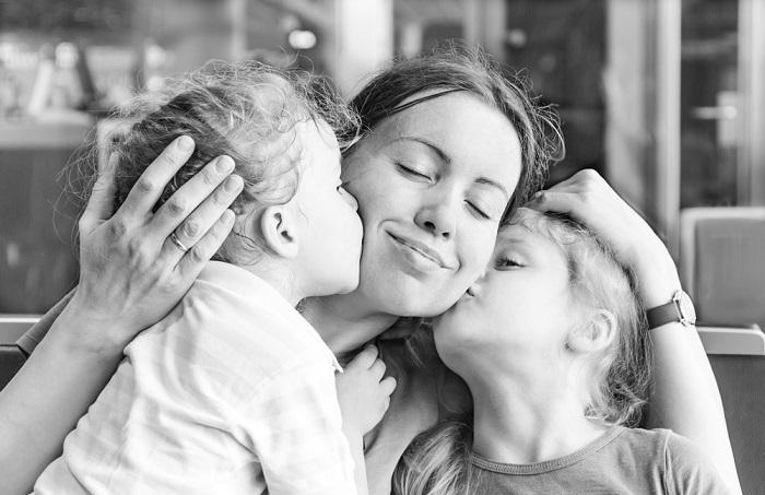 buena madre besando a sus hijos