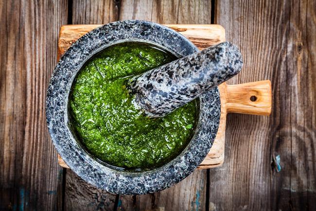 Preparando un delicioso pesto en mortero con ingredientes como albahaca y ajo