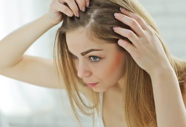 Mujer mirándose el cabello en el espejo