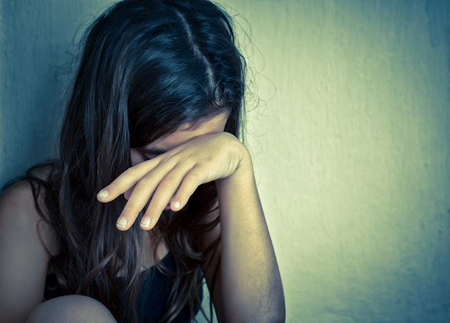 Chica con depresión crónica tapando su cara con su mano