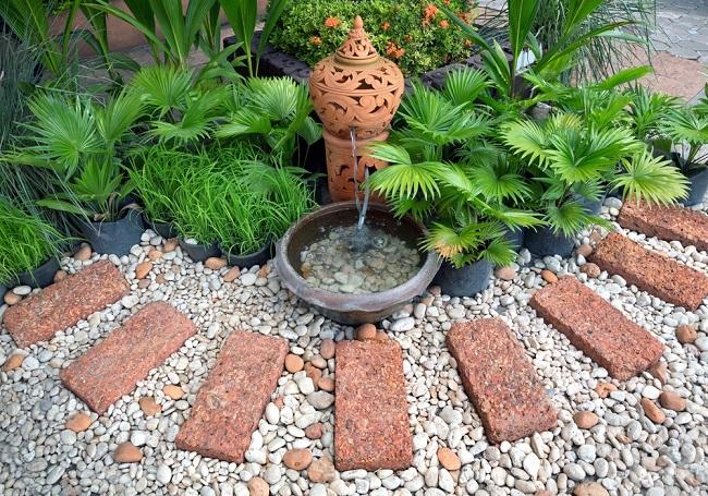 hacer jardinería en un espacio zen con piedras fuente agua