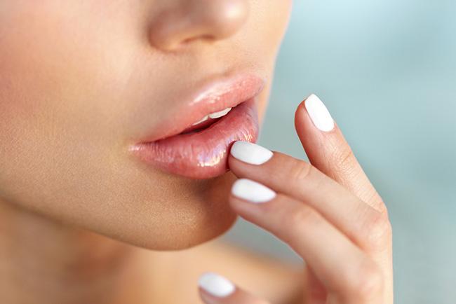 Mujer que se aplica maquillaje natural en los labios