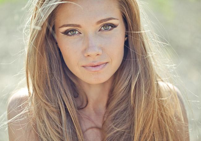 Mujer que usa maquillajes naturales en su rostro para lucir mejor