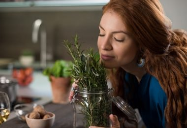 Mujer oliendo la frescura del romero que llena de aroma su hogar